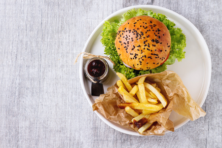 Photo pour Fresh homemade burger with black sesame seeds in white plate with french fries potatoes, served with ketchup sauce in glass jar over gray wooden surface. Top view - image libre de droit