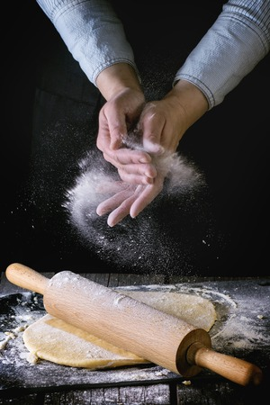 Female hands powdered by flour rolled out dough for pasta with wooden rolling pin over wooden kitchen table. Dark rustic style.