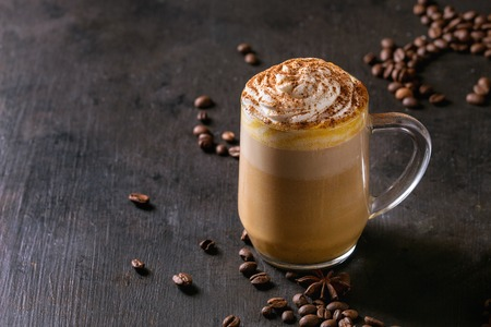 Photo pour Glass of spicy pumpkin latte with whipped cream and cinnamon standing on black serving board. Coffee beans and spices above. Dark background. - image libre de droit
