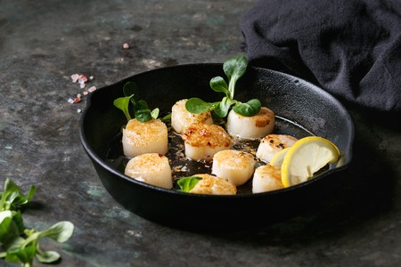 Photo pour Fried scallops with butter lemon spicy sauce in cast-iron pan served with green salad and textile napkin over old dark metal background. - image libre de droit
