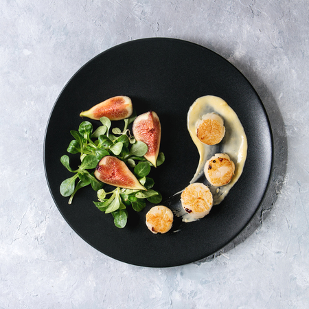 Photo pour Fried scallops with lemon, figs, sauce and green salad served on black plate over gray texture background. Top view, copy space. Plating, fine dining. Square image - image libre de droit