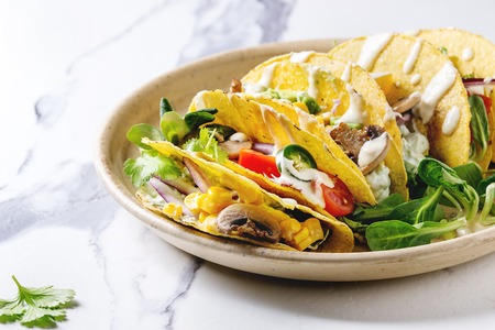 Foto de Variety of vegetarian corn tacos with vegetables, green salad, chili pepper served on ceramic plate with tomato and cream sauces with ingredients above on white marble kitchen table. Close up - Imagen libre de derechos