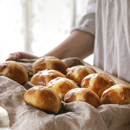 Photo pour Homemade Easter traditional hot cross buns on wooden tray with textile in female hands. Window at background. Natural day light. Rustic style. Square image - image libre de droit