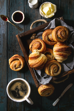 Photo pour Variety of homemade puff pastry buns cinnamon rolls and croissant served with coffee cup, jam, butter as breakfast over dark plank wooden background. Flat lay, space - image libre de droit