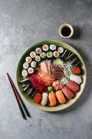 Photo pour Sushi Set nigiri sashimi and sushi rolls in ceramic serving plate with salad, soy sauce and chopsticks over grey concrete background. Flat lay, space. Japan menu - image libre de droit