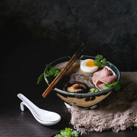 Foto de Traditional Japanese Noodle Soup with shiitake mushroom, egg, sliced beef and greens served in ceramic bowl with wooden chopsticks and white spoon on cloth over dark table. Asian style dinner. Square image - Imagen libre de derechos
