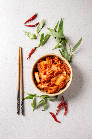Photo for Korean traditional fermented appetizer kimchi cabbage salad in ceramic bowl with shopsticks and Vietnamese oregano greens over grey spotted background. Flat lay, space. - Royalty Free Image