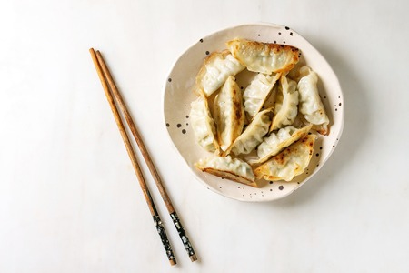 Foto de Fried asian dumplings Gyozas potstickers in white ceramic plate served with chopsticks and soy spring onion sauce over white marble background. Flat lay, space. Asian dinner - Imagen libre de derechos