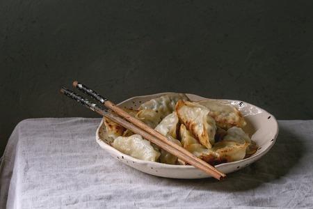 Foto de Fried asian dumplings Gyozas potstickers in white ceramic plate served with chopsticks over linen table cloth. Asian dinner - Imagen libre de derechos