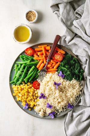 Photo pour Couscous with parboiled vegetables baby carrots, green beans, sweet corn, spinach served in ceramic plate with tomatoes, sesame and edible flowers. Vegan food. White marble background. Flat lay, space - image libre de droit