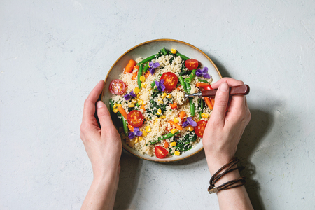 Photo pour Couscous with parboiled vegetables baby carrots, green beans, sweet corn, spinach in ceramic plate with tomatoes, sesame and edible flowers. Vegan food. Grey concrete background. Flat lay, space - image libre de droit