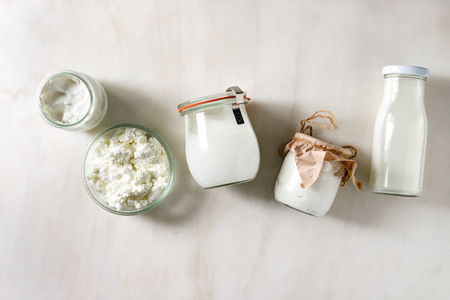 Photo pour Set of farm dairy produce cottage cheese, milk cream, plain yogurt in reusable eco friendly glass jars and bottle in row over white marble background. Flat lay, space - image libre de droit