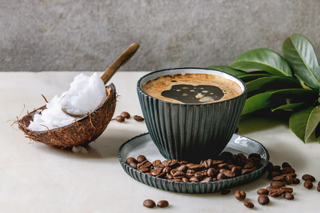 Photo pour Bulletproof coffee. Keto diet coffee in blue ceramic cup with organic coconut cold press oil in spoons with beans and green branch on white marble table. Grey wall at background. - image libre de droit