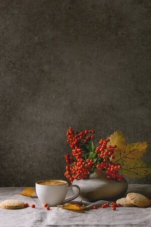 Photo pour Cup of espresso coffee standing on linen table cloth with yellow autumn leaves, berries in ceramic vase, coffee beans and shortbread cookies with dark wall at background. Fall concept. Copy space - image libre de droit
