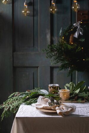 Foto de Christmas or New year table setting with empty ceramic plates, napkins, Christmas thuja wreath, luminous garland and burning candles on white tablecloth. Holiday mood - Imagen libre de derechos