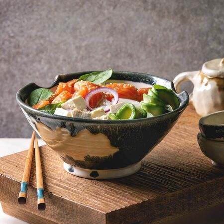 Foto de Poke bowl with soy sauce marinated salmon, rice, avocado and tofu cheese served in ceramic bowl with chopsticks and teapot on japanese wooden serving table over white marble. - Imagen libre de derechos