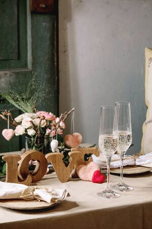 Photo for st. Valentines day or wedding romantic table setting with wooden letters love, needle felted hearts, ceramic plates, bouquet of pink roses, couple glasses of champagne on natural linen tablecloth. - Royalty Free Image