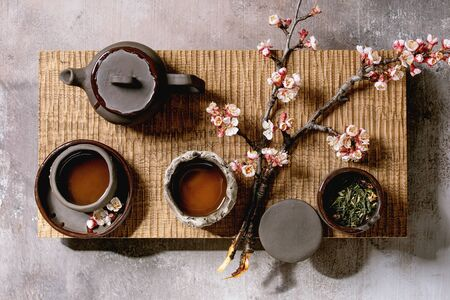 Photo pour Tea drinking wabi sabi japanese style dark clay cups and teapot on wooden tea table with blooming cherry branches. Grey texture concrete background. Flat lay, space - image libre de droit