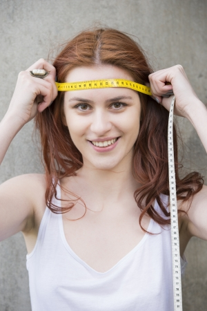 Young woman holding measuring tape on her forehead