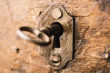 Old antique skeleton key in lock of wooden cabinet