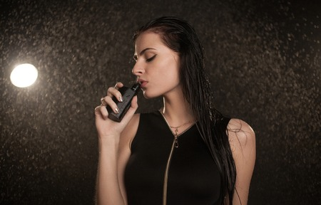 Young beautiful woman vaping e-cigarette. Water flowing on woman face.