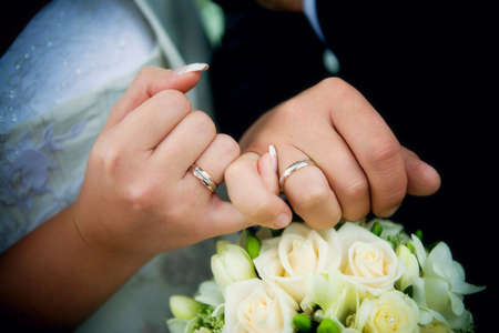 Hands with rings and wedding bouquet