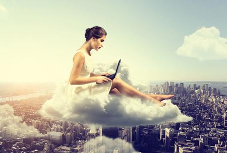 Photo pour Woman working o a cloud above the city - image libre de droit
