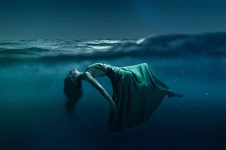 Photo pour Woman floating underwater - image libre de droit