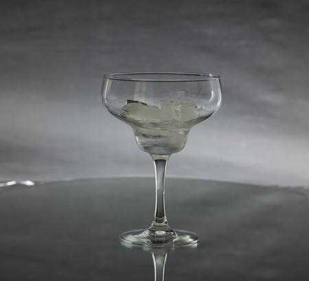 A glass with ice on a textured background