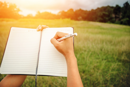 Photo pour Handwriting on notebook relax in the holiday. on a green pasture. - image libre de droit