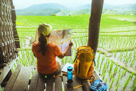 Photo for Asian woman travel nature. Travel relax. sit look map the balcony of the resort. View of the field on the Moutain in summer. Thailand - Royalty Free Image