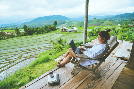 Photo pour Asian woman travel nature. Travel relax. sit work with a laptop the balcony of the resort. View of the field on the Moutain in summer. Thailand - image libre de droit