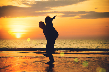 Photo pour Asian lovers happy on the beach with a beautiful sunset in background man lifting the woman. - image libre de droit