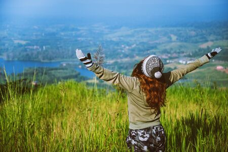 Asian woman travel nature. Travel relax. Standing natural touch grass on the Mountain at Khao-Kho. travel Thailand