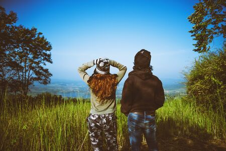 Couples travel nature. Travel relax. Standing natural touch grass on the Mountain at Khao-Kho. Travel honeymoon couple happy and enjoying a beautiful nature. travel Thailand