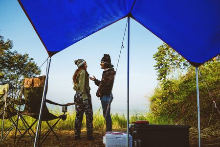 Couples travel camping tent in the holiday. Travel honeymoon couple happy and enjoying a beautiful nature on peak of foggy mountain.