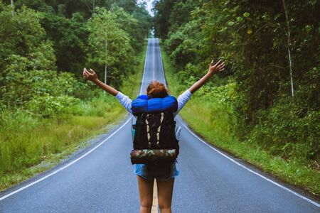Foto de Freedom traveler woman standing with raised arms and enjoying a beautiful nature On a country road. woman with backpack travel In the countryside On a mountain. - Imagen libre de derechos