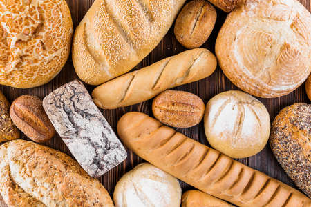 Foto für Different baking buns, croissants, gingerbread cookies. Delicious freshly baked bread on wooden background with place for text. Fresh loaves of bread And sliced breads containing sesame seeds. - Lizenzfreies Bild