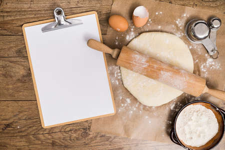 Photo for Flour and kitchen utensils whisk, baking dish, rolling pin with eggs on the table. Baking, cooking concept, top view with place for text. - Royalty Free Image