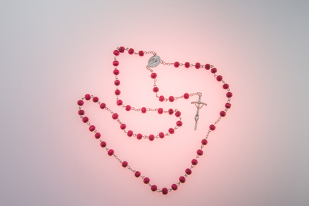 bead rosary on pink  background
