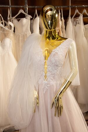 Foto per Wedding dress on a golden mannequin - Immagine Royalty Free