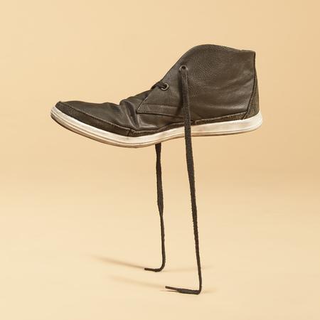 Photo pour Green shoe standing in its laces. Concept photo manipulation. - image libre de droit
