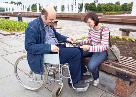 woman and man on an wheelchair play a chess