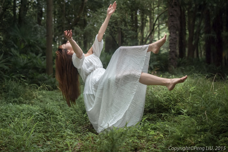 Beautiful woman falling onto the forest