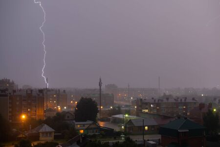 Photo pour Beautiful and powerful lightning strike over dark gray sky in night city. - image libre de droit