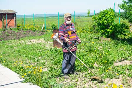 Foto de Elderly man mows grass in his house with an electric trimmer. Taking care of garden. - Imagen libre de derechos