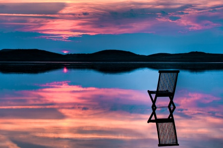 Scenic view of sunset over inlet and hills with a chair in the calm water, with reflections of sunset and chair. Symbolizing peace, loneliness or emptyness