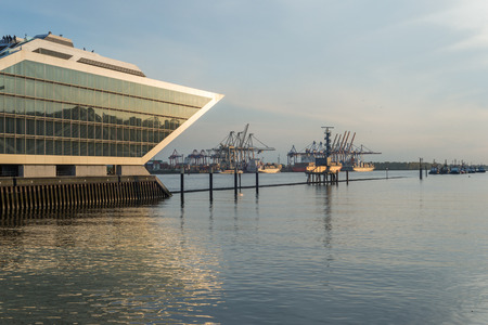 The Dockland Hamburg Altona is the old fishing harbor in Hamburg. Now there are modern office buildings at the Elbe river. In the background the container port Burchardkai