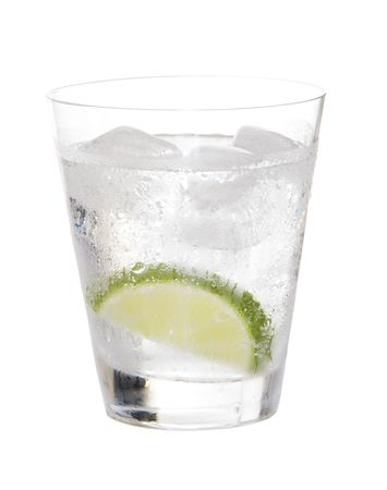 Glass of gin and tonic on ice with lime on white background