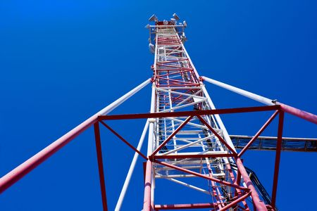 Cell phone and tv communications mast with cloudy blue sky space